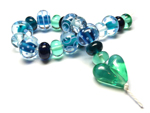 The patterned beads have cores of Tuscan Teal and Trade Winds encased in Effetre Pale Aquamarine and are decorated with Effetre Periwinkle. The heart is CiM Absinthe.